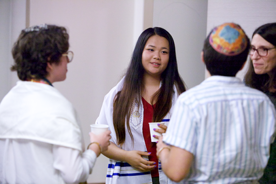 Diverse group of people wearing tallit and talking after Shabbat services