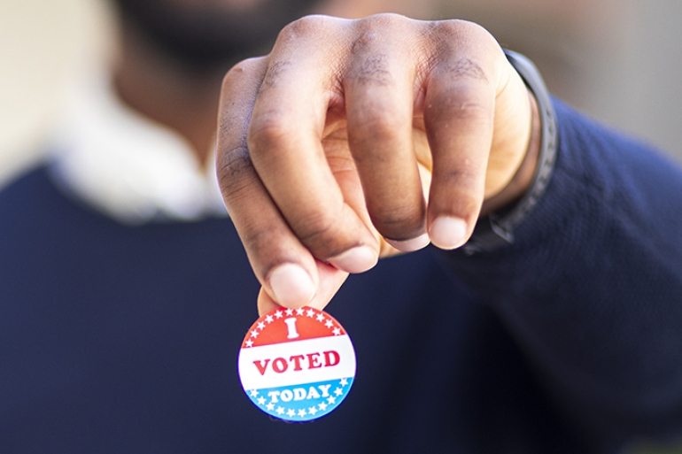Person holding up VOTE pin