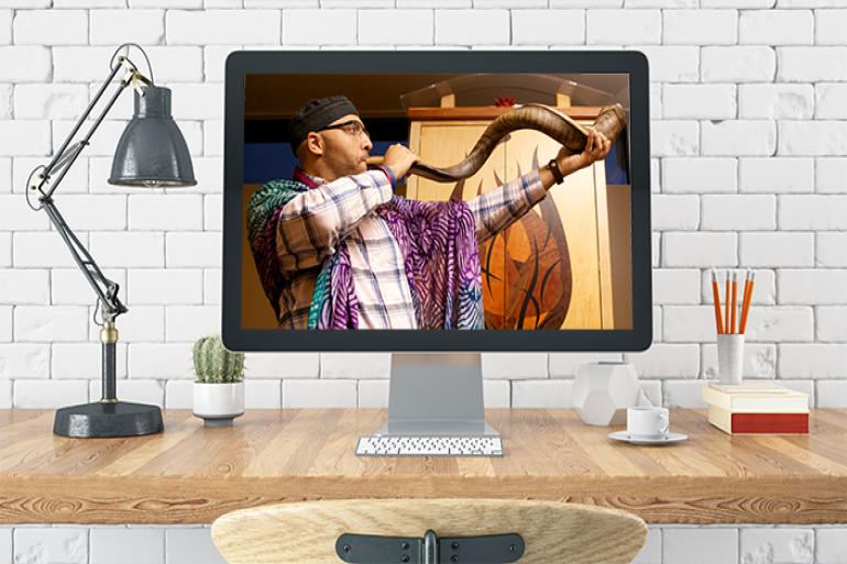 man blowing shofar on a computer screen