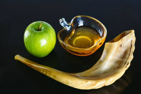 Shofar with a green apple and a bowl of honey on a black background