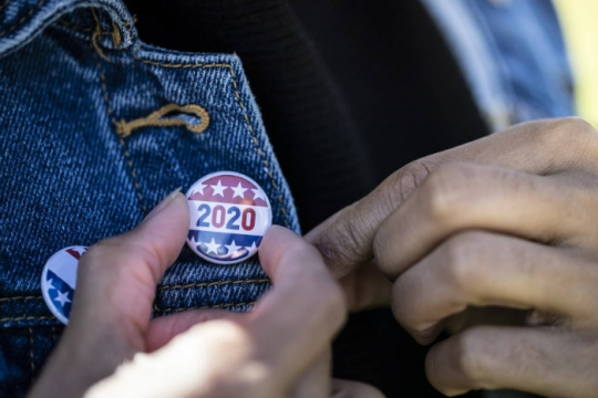 Closeup of a hand affixing a red white and blue 2020 button to a denim jacket