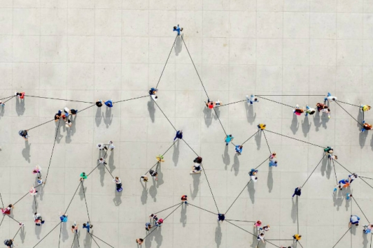 Aerial view of people standing spaced apart with line connecting them as if to represent connectivity despite distance