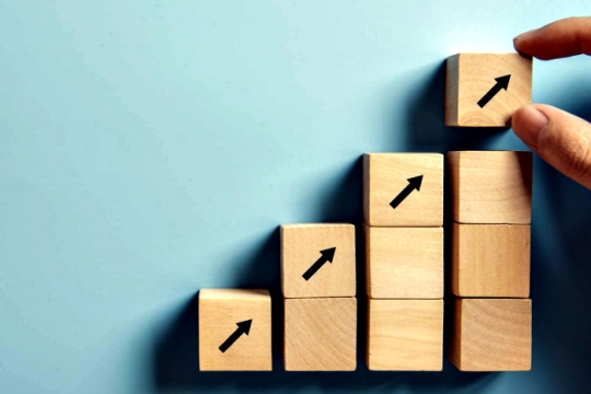 Building blocks in an upward trajectory with arrows pointing up