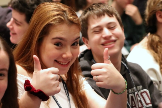 Smiling teen girl with two thumbs up