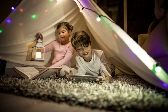 Children with books under makeshift tent indoors