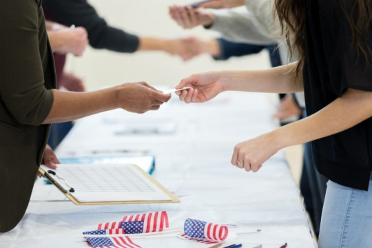 Multiple sets of hands over a voter registration table