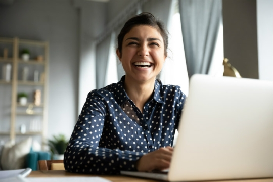 Smiling woman sitting at a laptop in her home