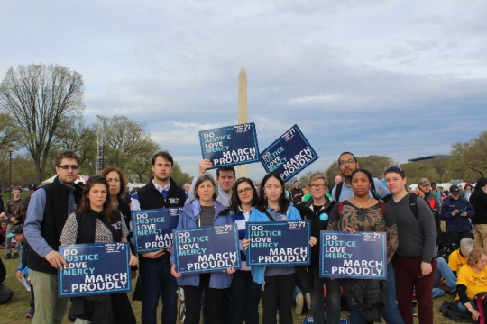 Group of people holding Jewish justice signs standing in front of the Washington Monument