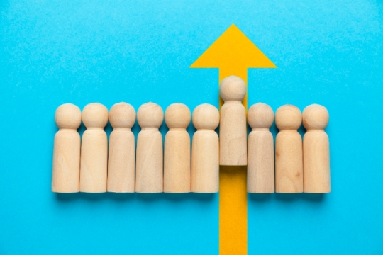 Line of wooden pegs shaped like people against a blue background with one peg moving upward against a yellow arrow as if to signify leadership