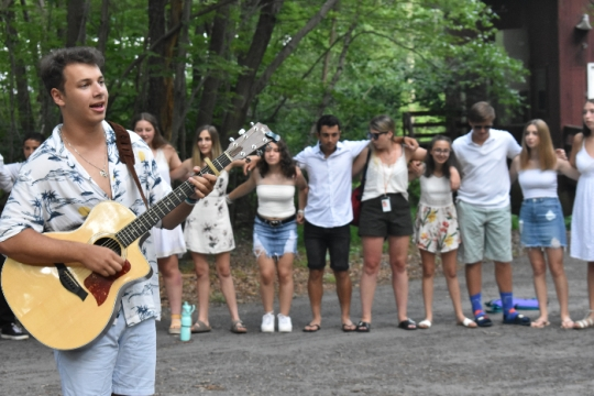 Summer camp staffer playing the guitar while standing in a circle of campers with their arms around one another