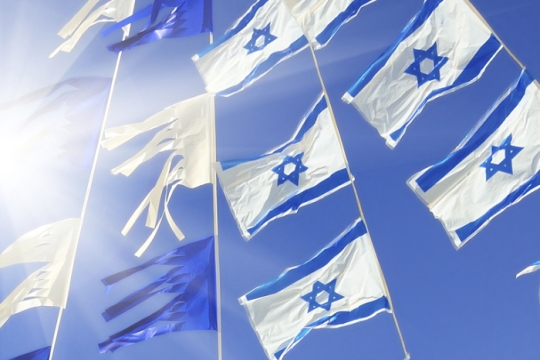 Israeli flags strung up across a blue sky