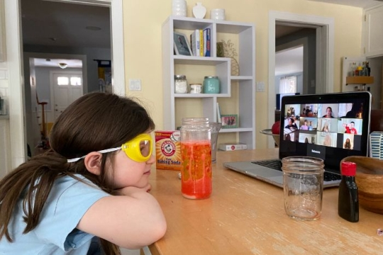 Young girl wearing googles while watching a Zoom screen surrounded by materials for conducting a science experiment