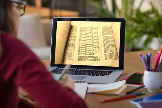 Student taking a Judaism class online and looking at image of Torah on computer