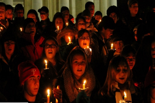 Lighted faces of teenagers holding candles in the dark