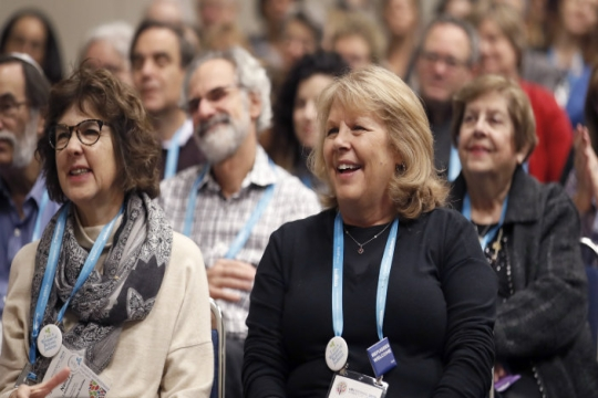 A group of people smiling and clapping in an audience at the URJ Biennial