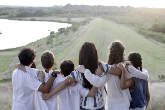 Campers dressed in Shabbat whites with their arms around one another as they face a nature scene