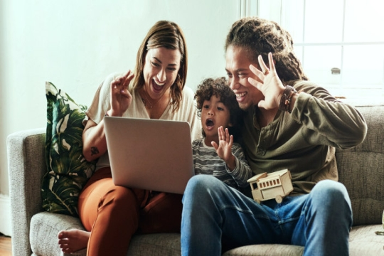 A smiling couple and their young son waving happily at a computer screen while sitting together on a couch inside a home
