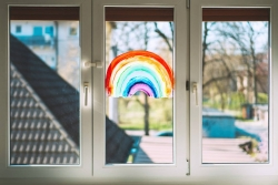 Three pane window with a rainbow fingerprinted onto it and facing the outdoors