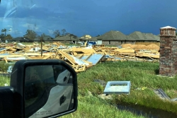 Houses wiped out by Hurricane Laura as photographed from the inside of a car with the side mirror visible