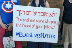 White womans hands holding a sign in Hebrew and English reading YOU SHALL NOT STAND IDLE UPON THE BLOOD OF YOUR FELLOW and concluding with the phrase BLACK LIVES MATTER