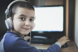 Boy wearing headphones and looking over his shoulder from a desk with a computer