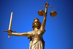 Statue of Justice -- blindfolded with a sword in one hand and a scale in the other