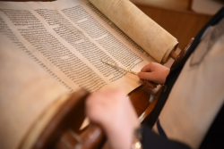 Open Torah scroll with reading pointing a silver yad at the text