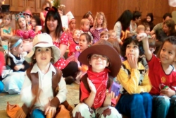 Smiling young children wearing Purim costumes and sitting on the bimah in a synagogue