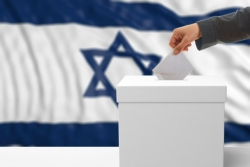 Hand placing a ballot in ballot box; Israeli flag in the background