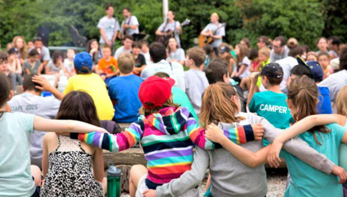 Campers with their arms around one another and their backs to the camera during an outdoor Shabbat service