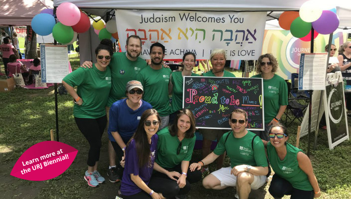 Group of people wearing synagogue shirts and standing in front of a rainbow welcome banner