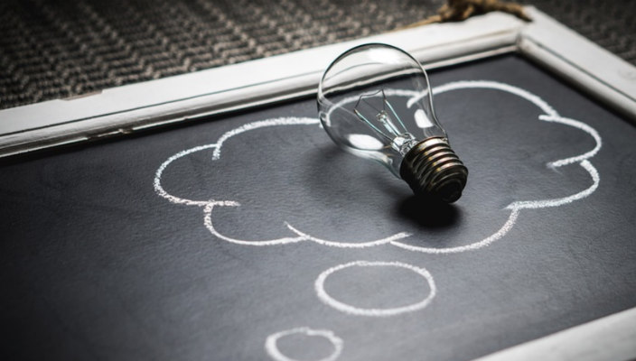 Light bulb sitting atop a thought bubble drawn in chalk on a chalkboard