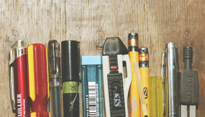 Various pens, pencils, and screwdrivers, side-by-side in front of a wooden background