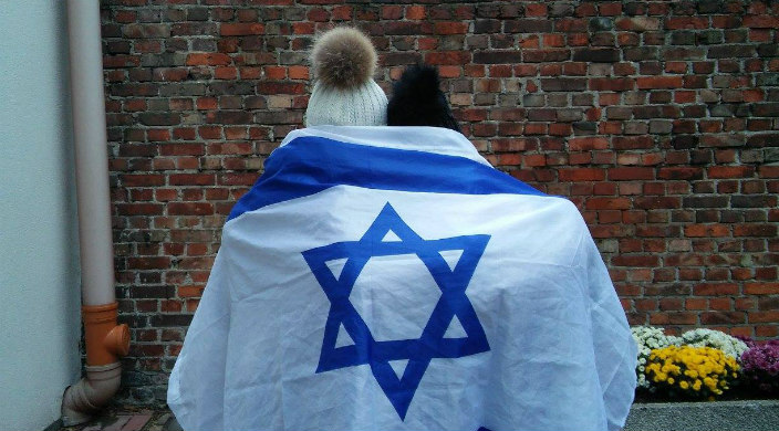 Two students, backs to the camera, wrapped together in an Israeli flag