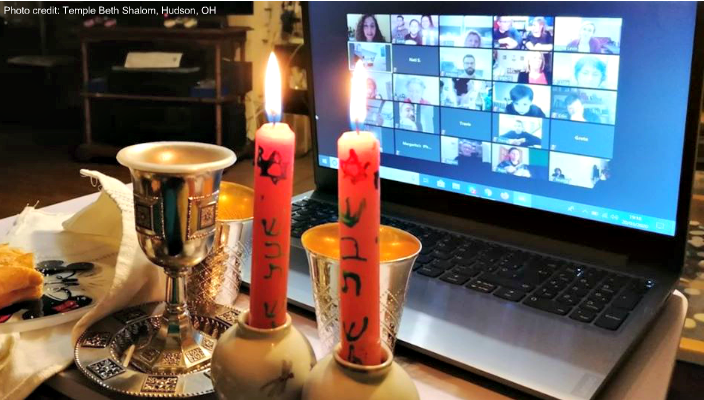 Shabbat candles next to a Zoom screen