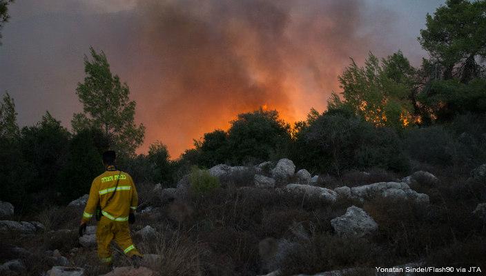 An Israeli firefighter watches a blaze from afar
