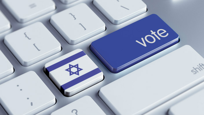 Computer keyboard with blue enter key that says Vote; key to the left is Israeli flag