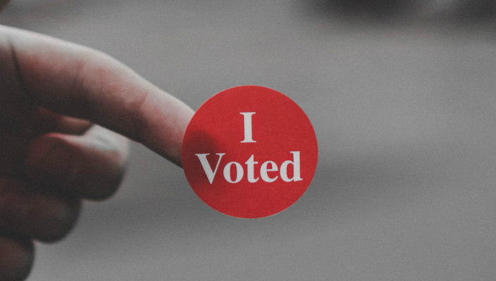 Finger holding a red and white sticker that reads I VOTED