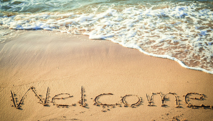 welcome written in sand on the beach