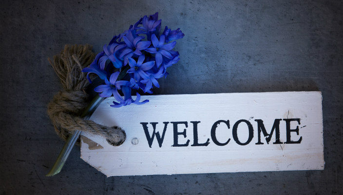 Welcome written on a wooden sign with flowers