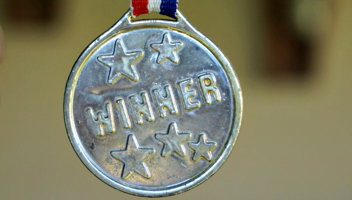 Silver medal with the word WINNER on it