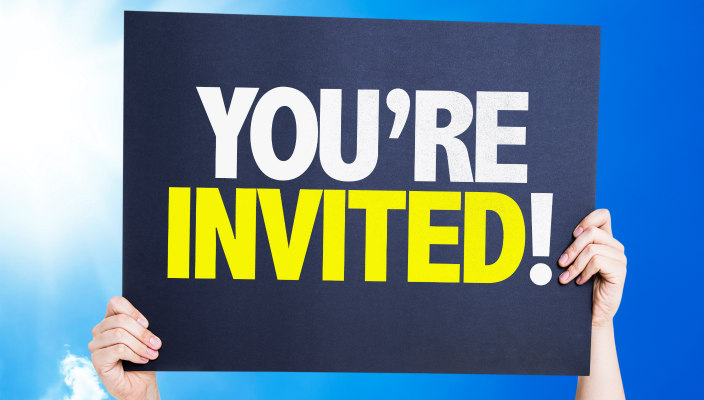 Sign that says You're Invited held overhead