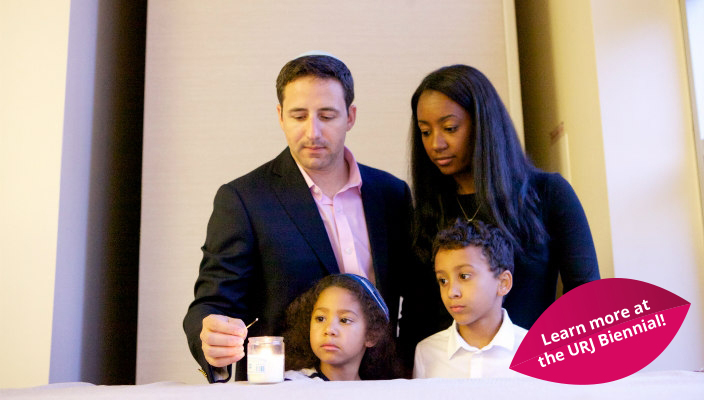Young couple and their children lighting the Shabbat candles together